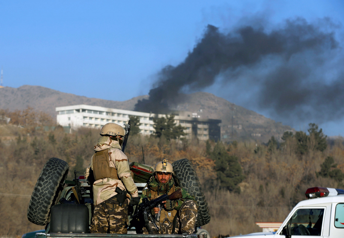 Afghan security forces keep watch as smoke rises from the Intercontinental Hotel in Kabul, Afghanistan