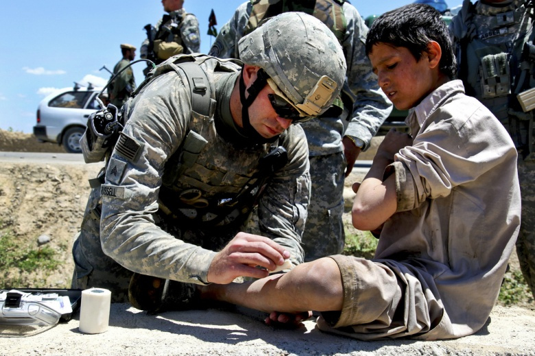 U.S. Army Sgt. John Russell gives a small child medical care in Logar Province, Afghanistan.