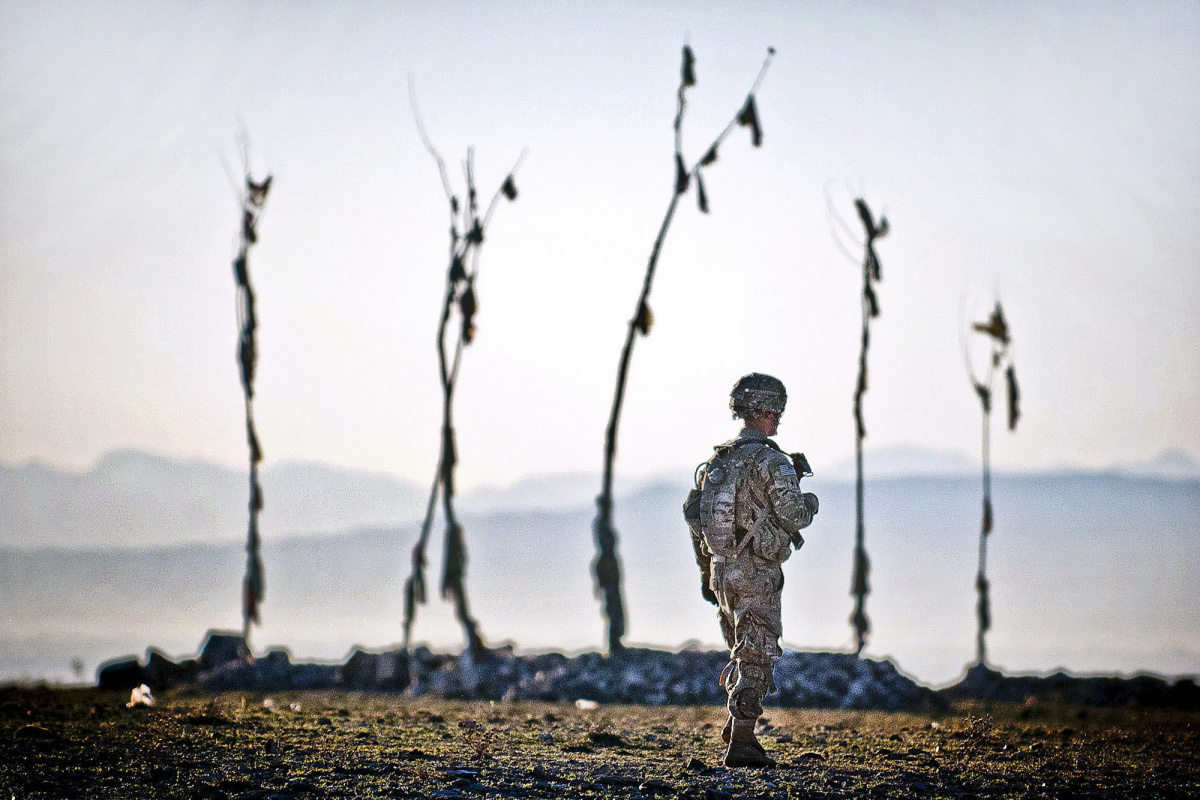 Spc. Jon Saladin, a paratrooper with the 82nd Airborne Division's 1st Brigade Combat Team, walks past an Afghan graveyard during a U.S. – Afghan patrol