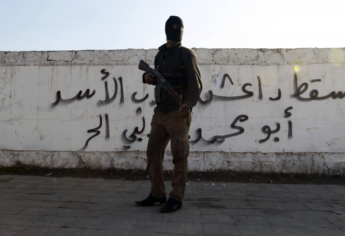 """A Free Syrian Army fighter carries his weapon as he stands in front of graffiti that reads """"Daesh (Islamic State of Iraq and the Levant ) down"""" at Masaken Hanano neighborhood in Aleppo"""
