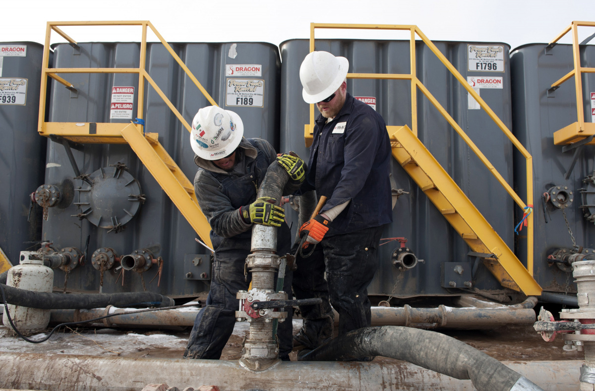 Mody Torres (L) and Josh Anderson of Select Energy Services connect hoses between a pipeline and water tanks at a Hess fracking site near Williston, North Dakota