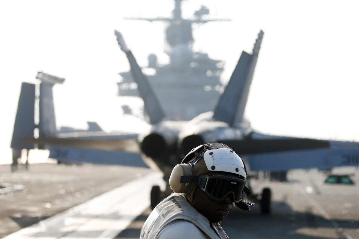 A U.S. Navy crew member looks at a F/A-18 Super Hornet fighter as it prepares for take off from the USS Ronald Reagan, a Nimitz-class nuclear-powered super carrier, during a joint naval drill between South Korea and the U.S., in the West Sea, South Korea