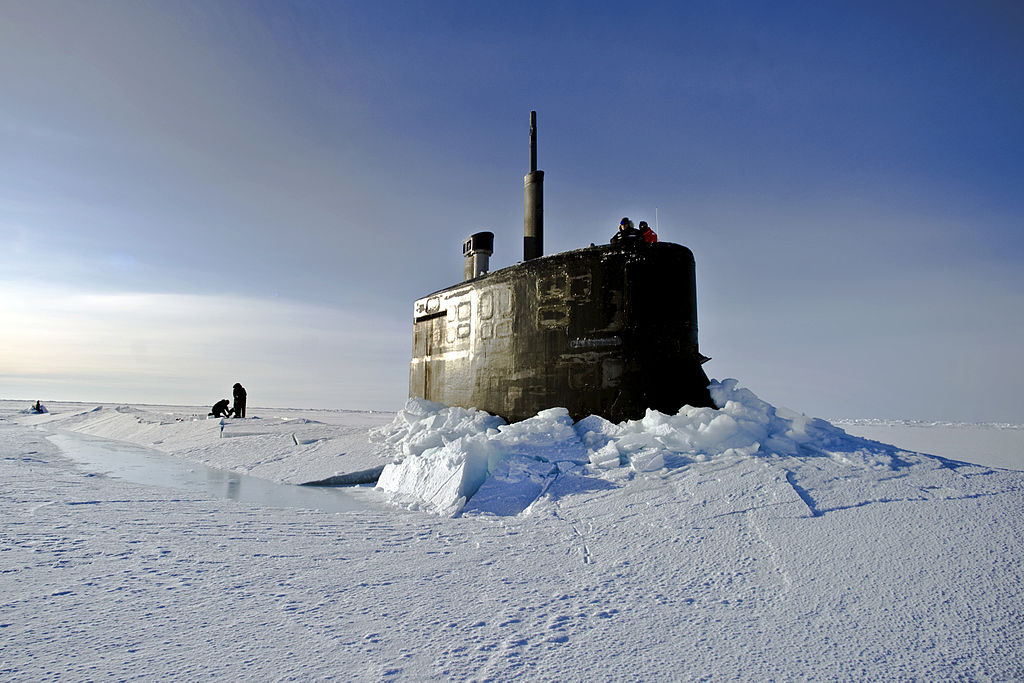 U.S. Navy sailors and members of the Applied Physics Laboratory Ice Station clear ice from the hatch of the USS Connecticut as it surfaces above the ice in the Arctic Ocean. Wikimedia Commons/Public domain