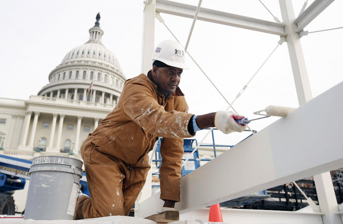 A worker paints a section of the inaugural platform in front of the Capitol in Washington