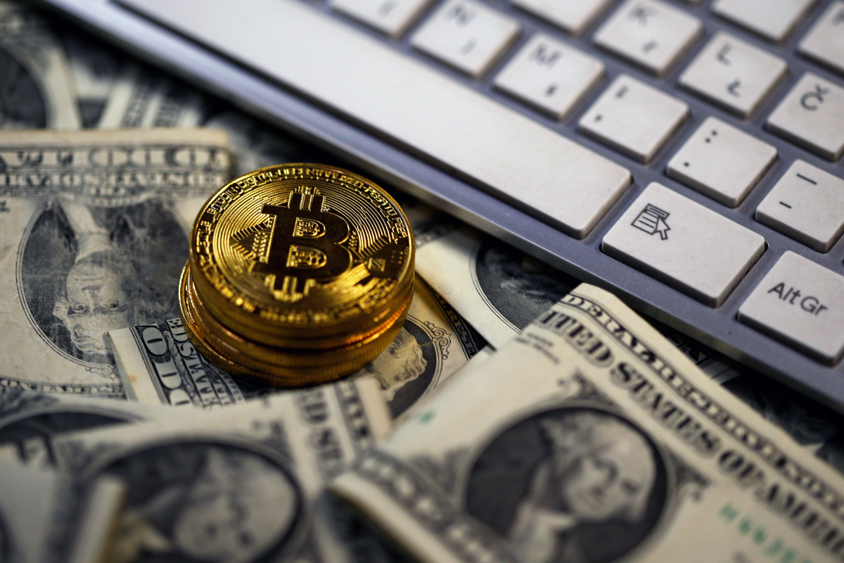 Bitcoin (virtual currency) coins placed on Dollar banknotes, next to computer keyboard, are seen in this illustration picture