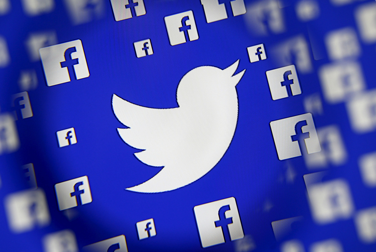 Logo of the Twitter and Facebook are seen through magnifier on display in this illustration taken in Sarajevo, Bosnia and Herzegovina
