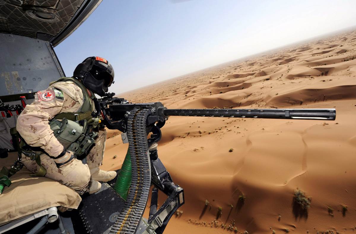 Canadian Forces door gunner Sergeant Chad Zopf leans out of a CH-146 Griffon helicopter during a training exercise in Kandahar district, Afghanistan