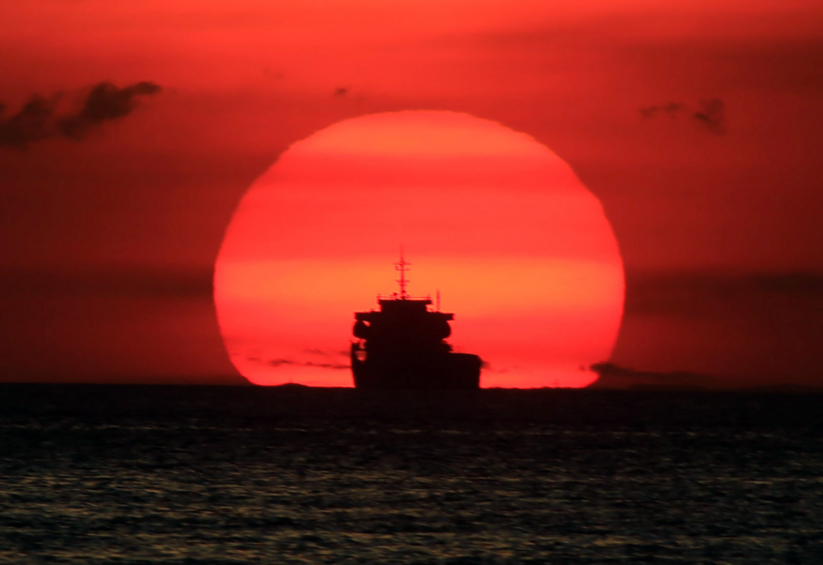 A cargo ship is silhouetted as the sun sets along the coast of Manila bay in Metro Manila, Philippines