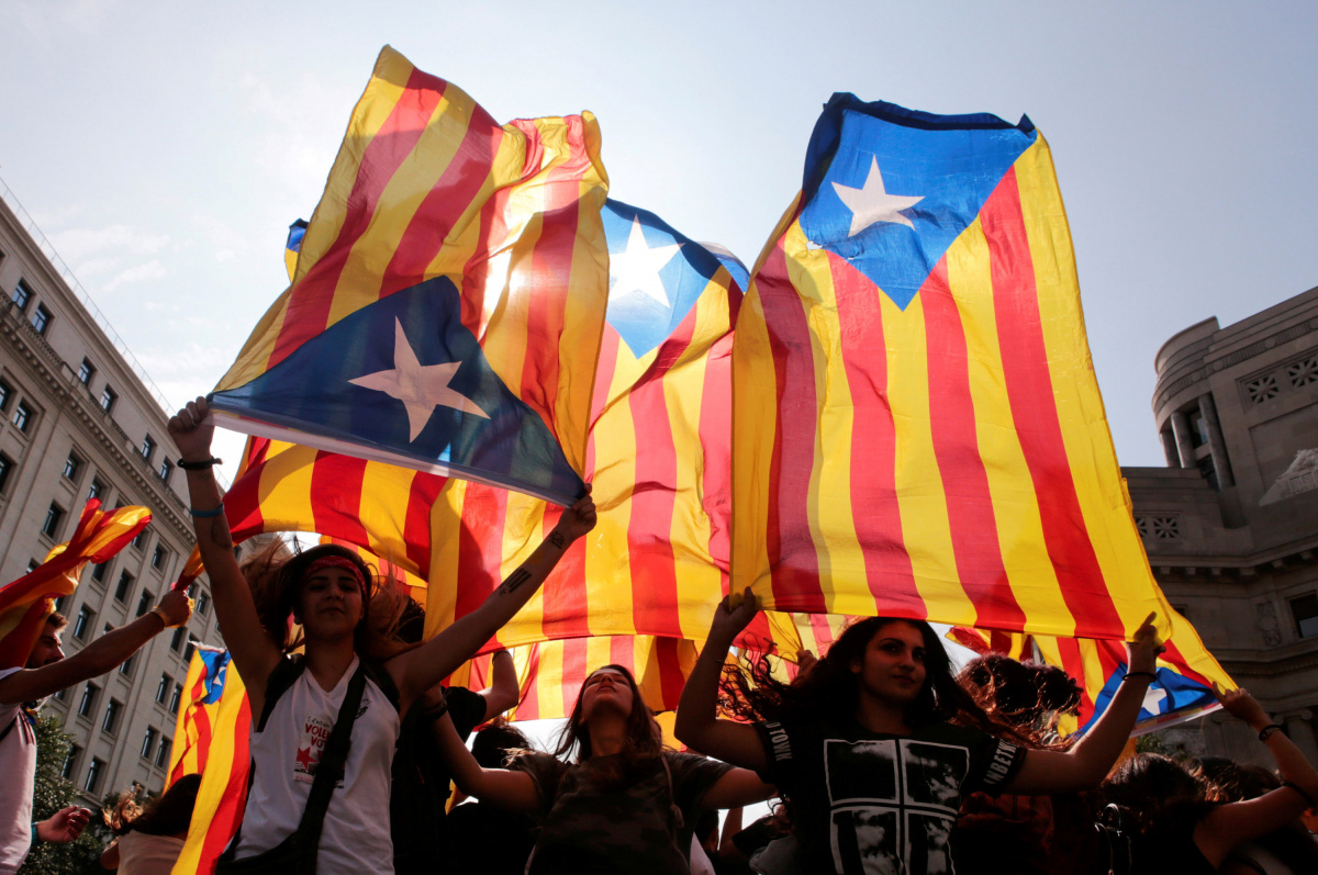 People hold on to Catalan separatist flags on top of an air vent during a demonstration two days after the banned independence referendum in Barcelona