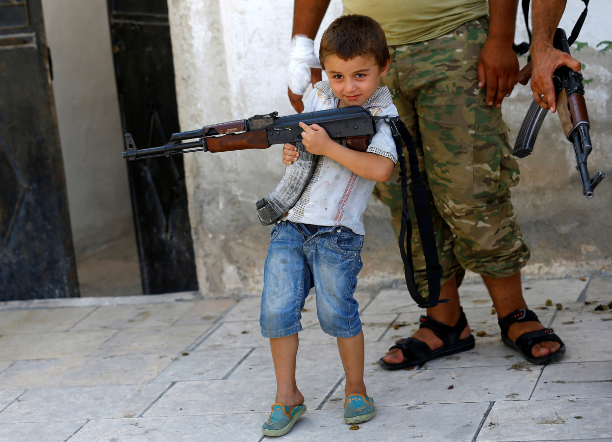 A boy holding a rifle stands next to a member of Turkish-backed Free Syrian Army (FSA) in the border town of Jarablus, Syria