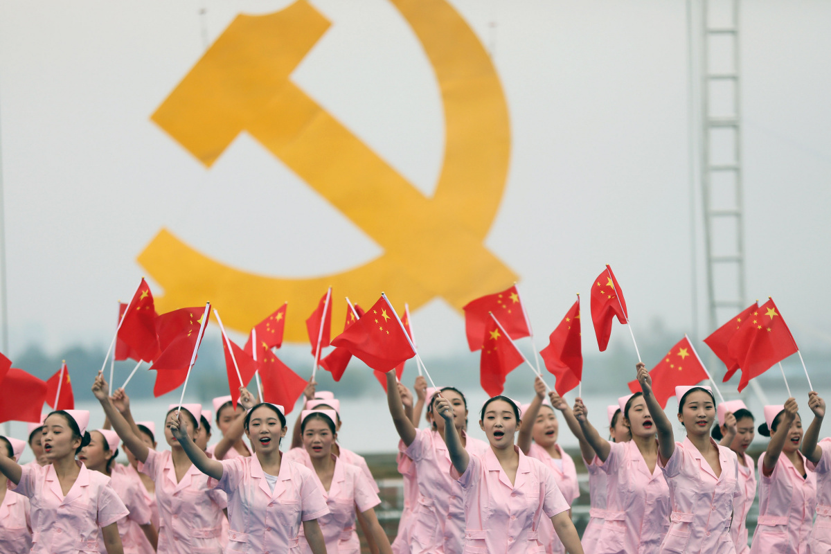 Nurses wave Chinese national flags during a performance to celebrate the upcoming 19th National Congress of the Communist Party of China in Huaibei, Anhui province, China