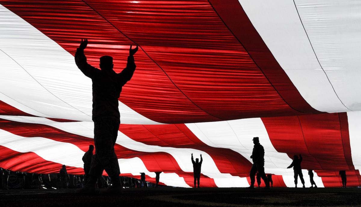 Airmen hold the American flag before the Las Vegas Bowl. DVIDSHUB/Public domain