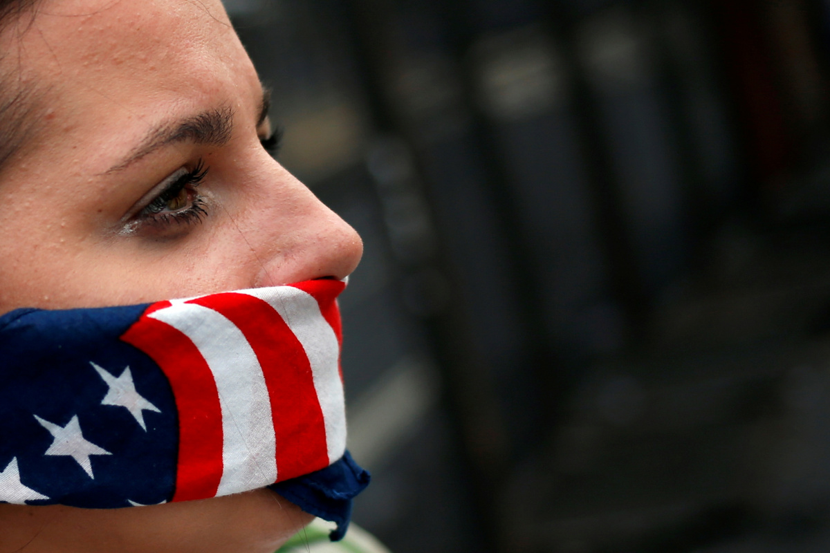 A supporter of U.S. Senator Bernie Sanders covers her mouth with a bandana in the colors of the American flag while standing along the perimeter fence of the 2016 Democratic National Convention in Philadelphia, Pennsylvania on July 28, 2016. REUTERS/Adrees Latif