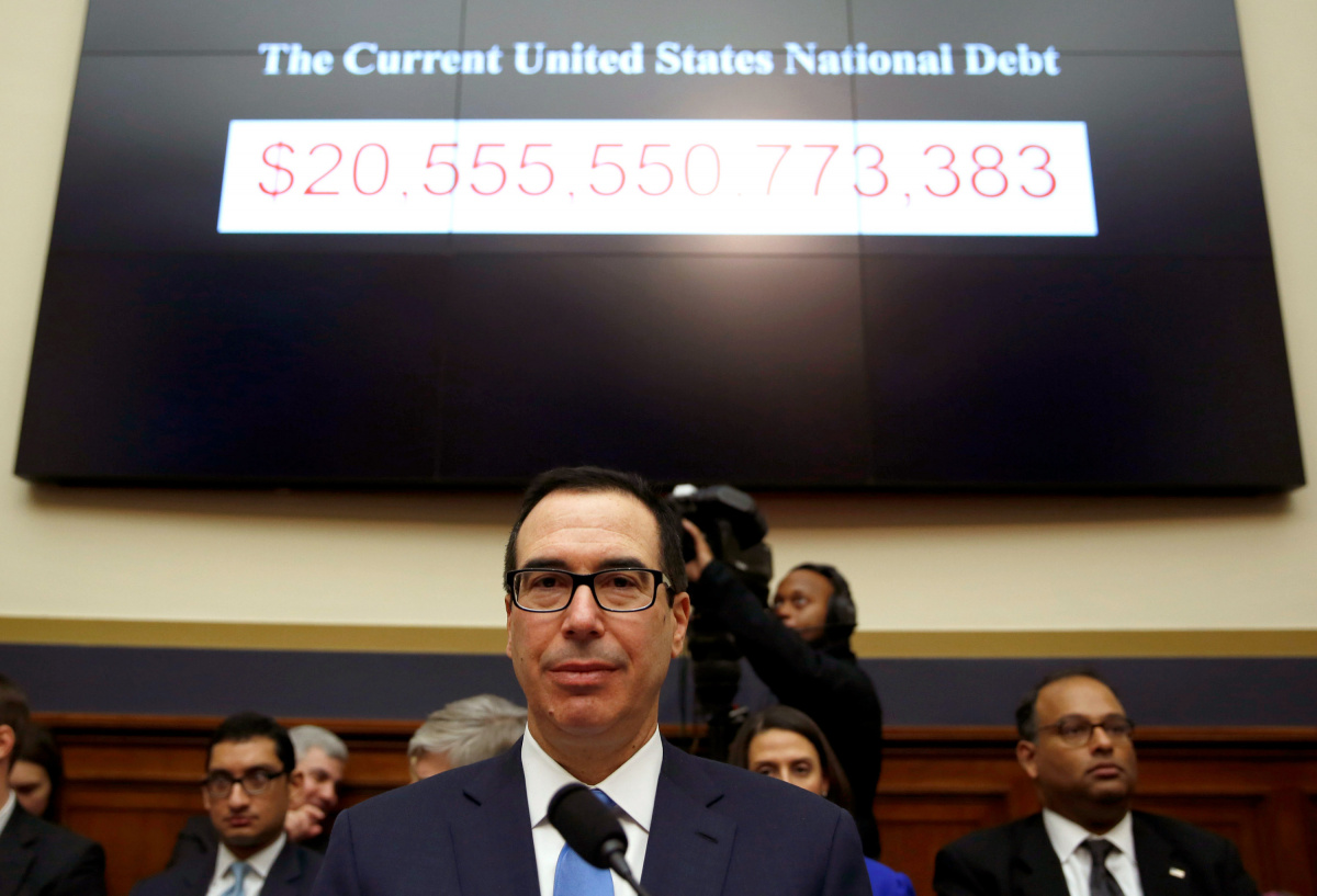 Treasury Secretary Mnuchin sits under a display of the U.S. national debt as he testifies to the House Financial Services Committee in Washington
