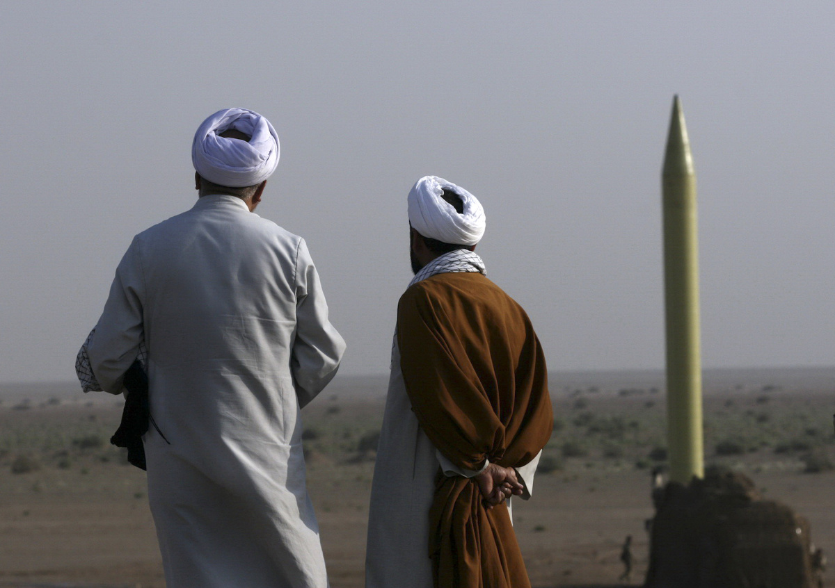 Two Iranian clerics stand near a surface to surface missile which is ready to be launched during a war game near the city of Qom