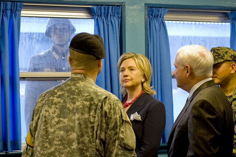 Secretary of State Hillary Rodham Clinton and Secretary of Defense Robert Gates in the DMZ, as a North Korean soldier watches. Wikimedia Commons/Public domain