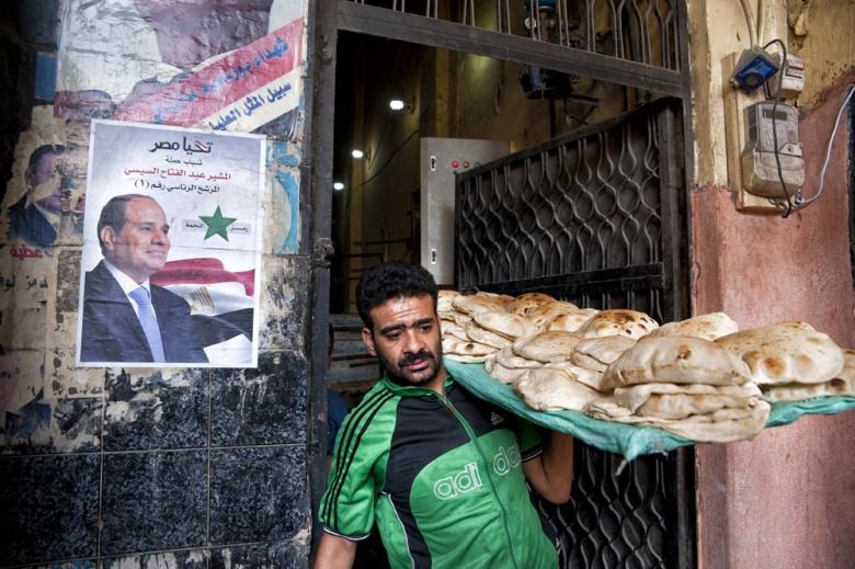 Baker in Egypt carrying bread past an image of Abdel Fattah el-Sisi. Wikimedia Commons/Mohamed Kamal