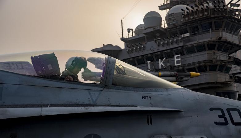 A pilot awaits in an F/A-18C Hornet taxis across the flight deck of the aircraft carrier USS Dwight D. Eisenhower. Flickr/U.S. Navy