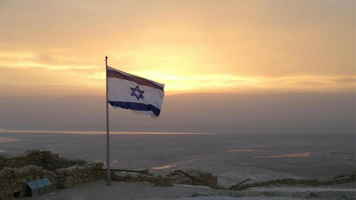 An Israeli flag flies at sunset.