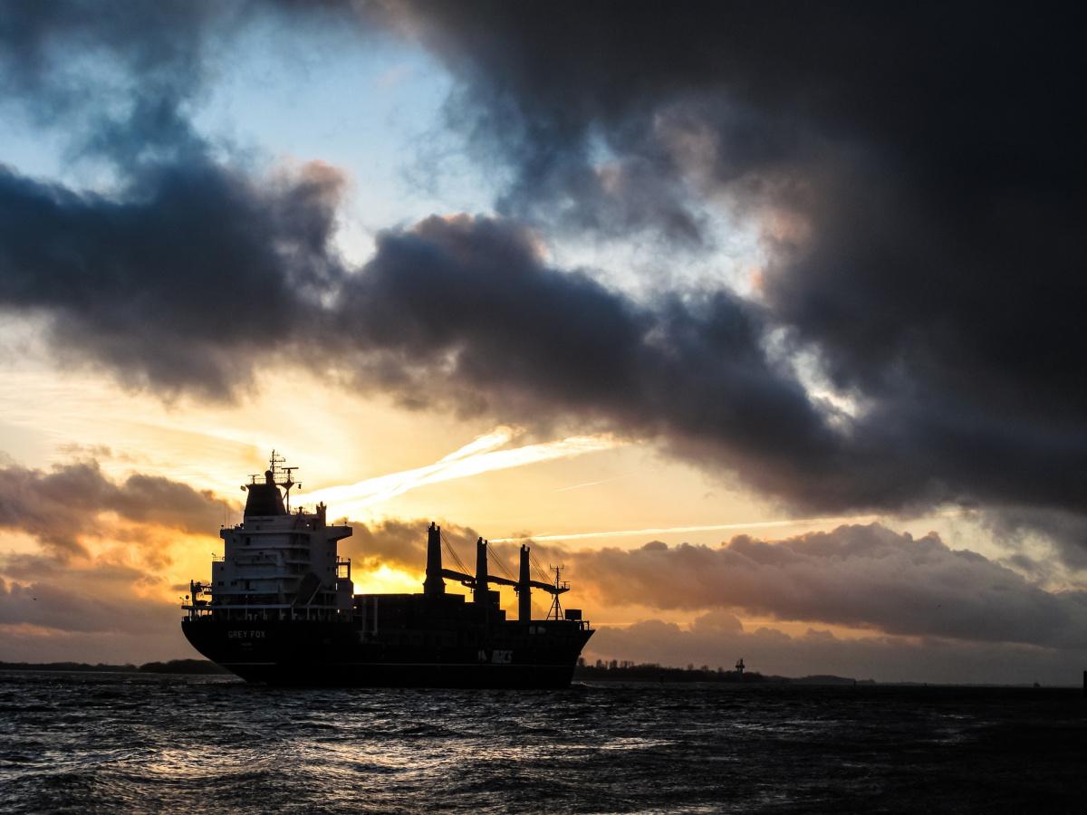 A ship sails at dusk.