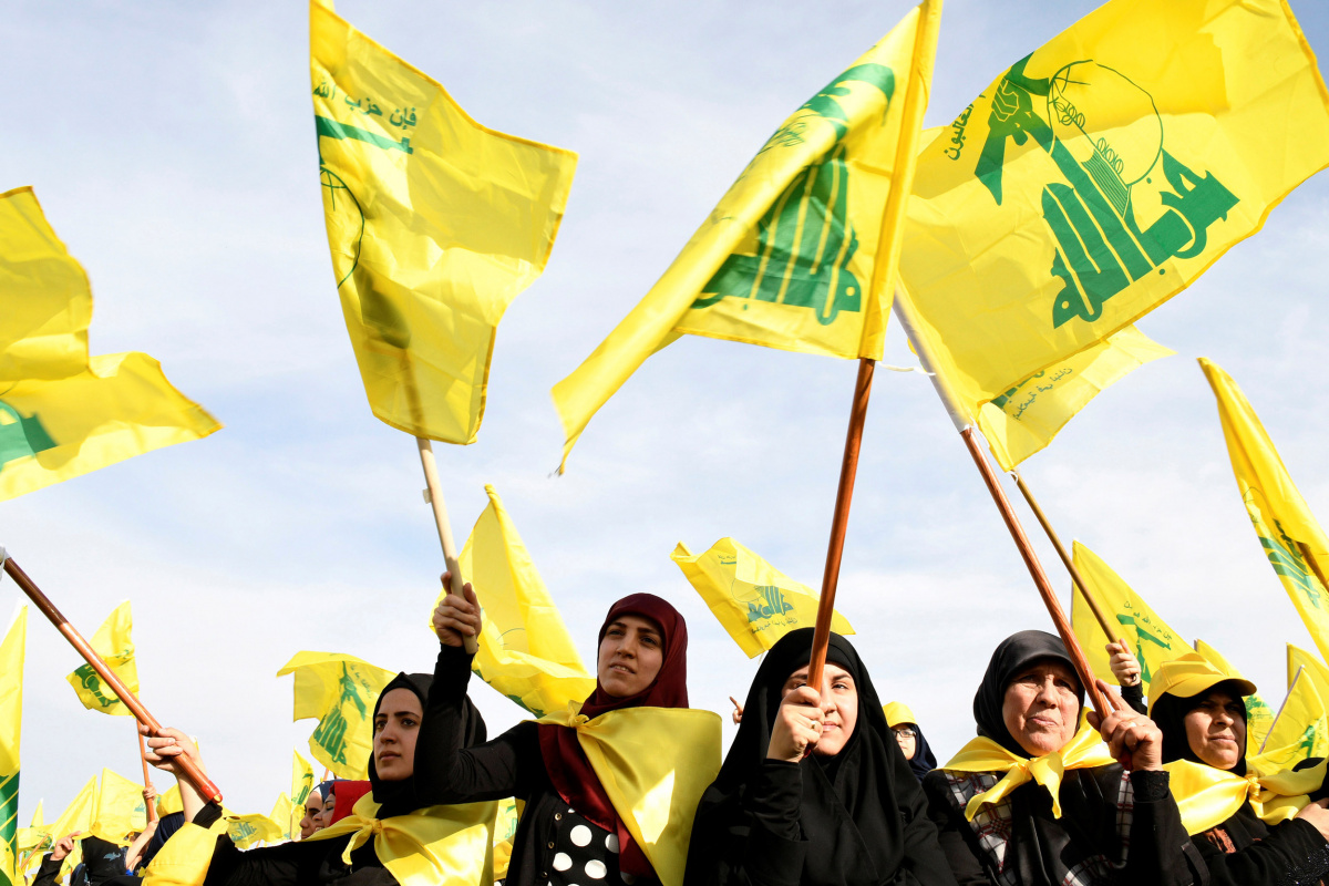 Women wave Hezbollah flags as they watch Lebanon's Hezbollah leader Sayyed Hassan Nasrallah appear on a screen during a live broadcast to speak to his supporters at an event marking Resistance and Liberation Day in the Bekaa Valley, Lebanon