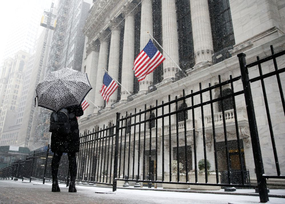 A woman looks up as snow begins to fall in front of the New York Stock Exchange, (NYSE) during the morning commute in New York City, U.S., February 7, 2018. REUTERS/Brendan McDermid
