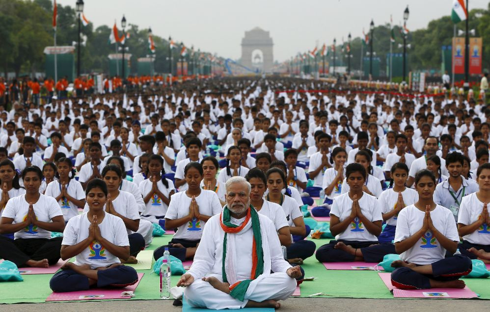 India's Prime Minister Narendra Modi performs yoga with others to mark the International Day of Yoga, in New Delhi, India, June 21, 2015. Modi led tens of thousands of people in the yoga session in the centre of the capital on Sunday to showcase the country's signature cultural export, which has prompted criticism of fomenting social divisions at home. REUTERS/Adnan Abidi