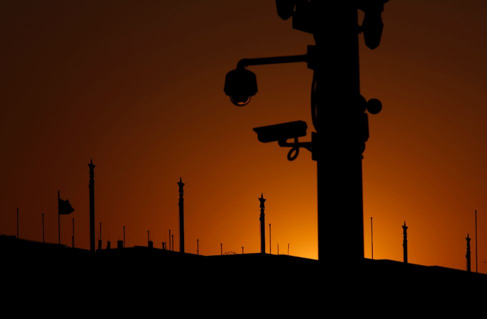 Security cameras on Tiananmen square and China's national flag at the Great Hall of the People, where the closing ceremony of the Chinese Communist Party plenum is going to be held on Tuesday, are silhouetted against the sunset in Beijing, November 11, 2013. Top leaders are meeting in secret in Beijing to plot an economic agenda for the next decade, and will be looking at pilot schemes in Chengdu and elsewhere that are testing land and residency reform for clues on what changes to make. REUTERS/Kim Kyung-Ho