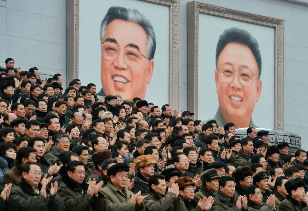 "North Koreans applaud in front of portraits of North Korea's founder Kim Il-sung (L) and late leader Kim Jong-il as they gather at a rally to celebrate the successful launch of the Unha-3 (Milky Way 3) rocket, which carried the second version of the Kwangmyongsong-3 satellite, in Pyongyang, in this picture released by Kyodo December 14, 2012. When North Korea's Kim Jong-un commemorates a year of his rule next week, he will be able to declare he has fulfilled the country's long-held dream of becoming a ""spac"