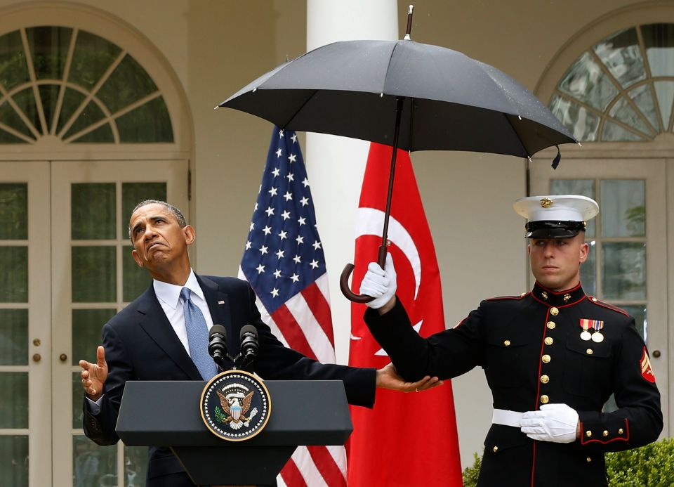 U.S. President Barack Obama checks to see if he still needs the umbrella held by a U.S. Marine to protect him from the rain during a joint news conference with Turkish Prime Minister Recep Tayyip Erdogan in the Rose Garden of the White House in Washington, May 16, 2013.