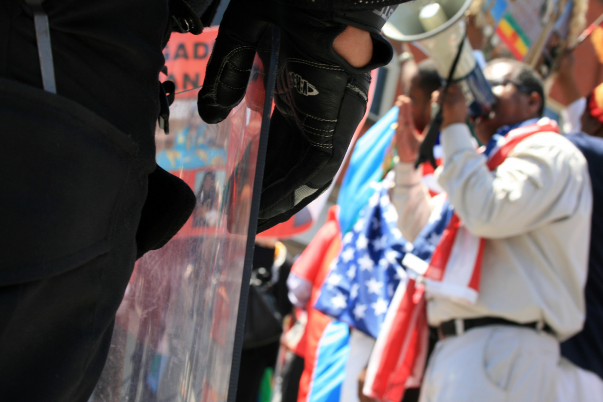 A Maryland State Police officer watches a man shout into a megaphone during a May 2012 G8 Summit protest in Thurmont, Maryland. Briefing Room Art/Maggie Ybarra.