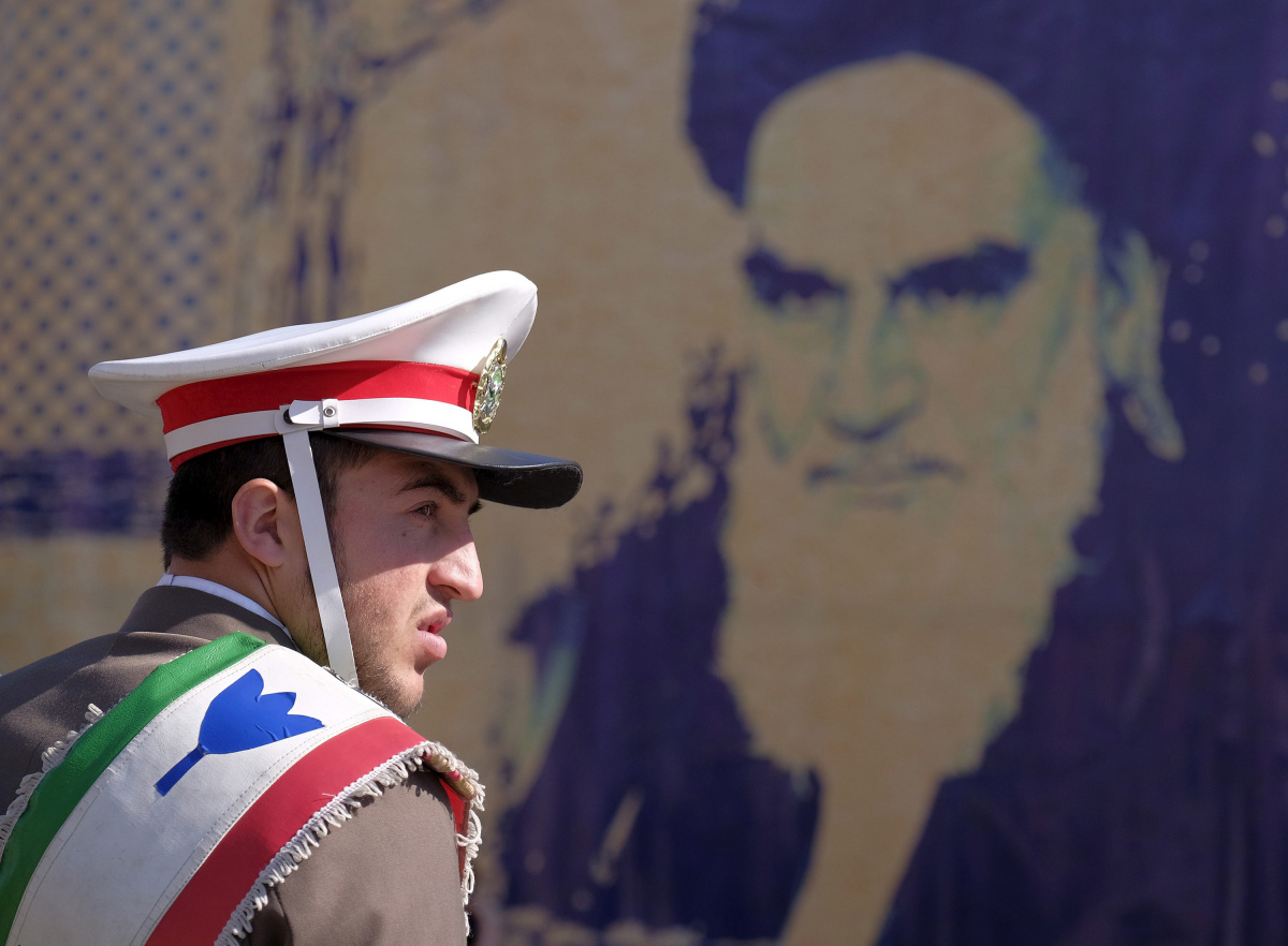 An Iranian soldier stands guard in front of a picture of Iran's late leader Ayatollah Ruhollah Khomeini during the anniversary ceremony of Iran's Islamic Revolution in Behesht Zahra cemetery