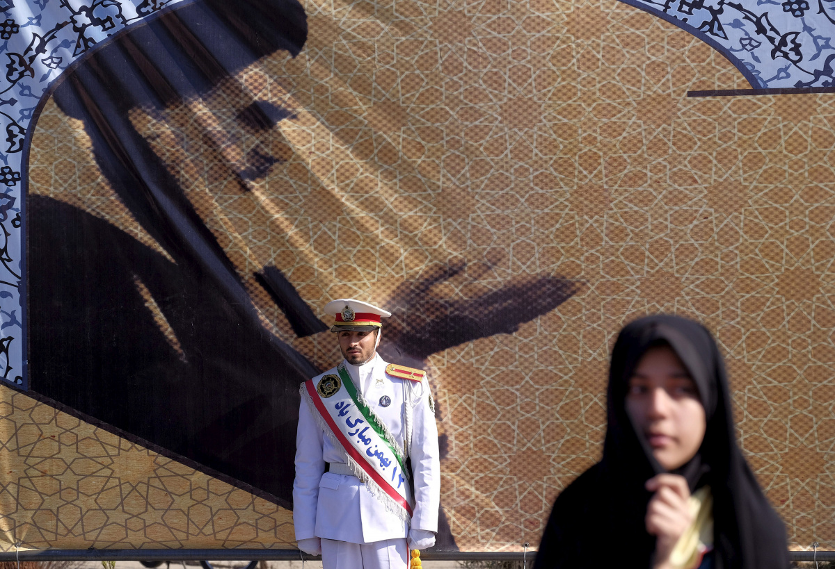 An Iranian soldier stands guard in front of a picture of Iran's late leader Ayatollah Ruhollah Khomeini during the anniversary ceremony of Iran's Islamic Revolution in Behesht Zahra cemetery, south of Tehran