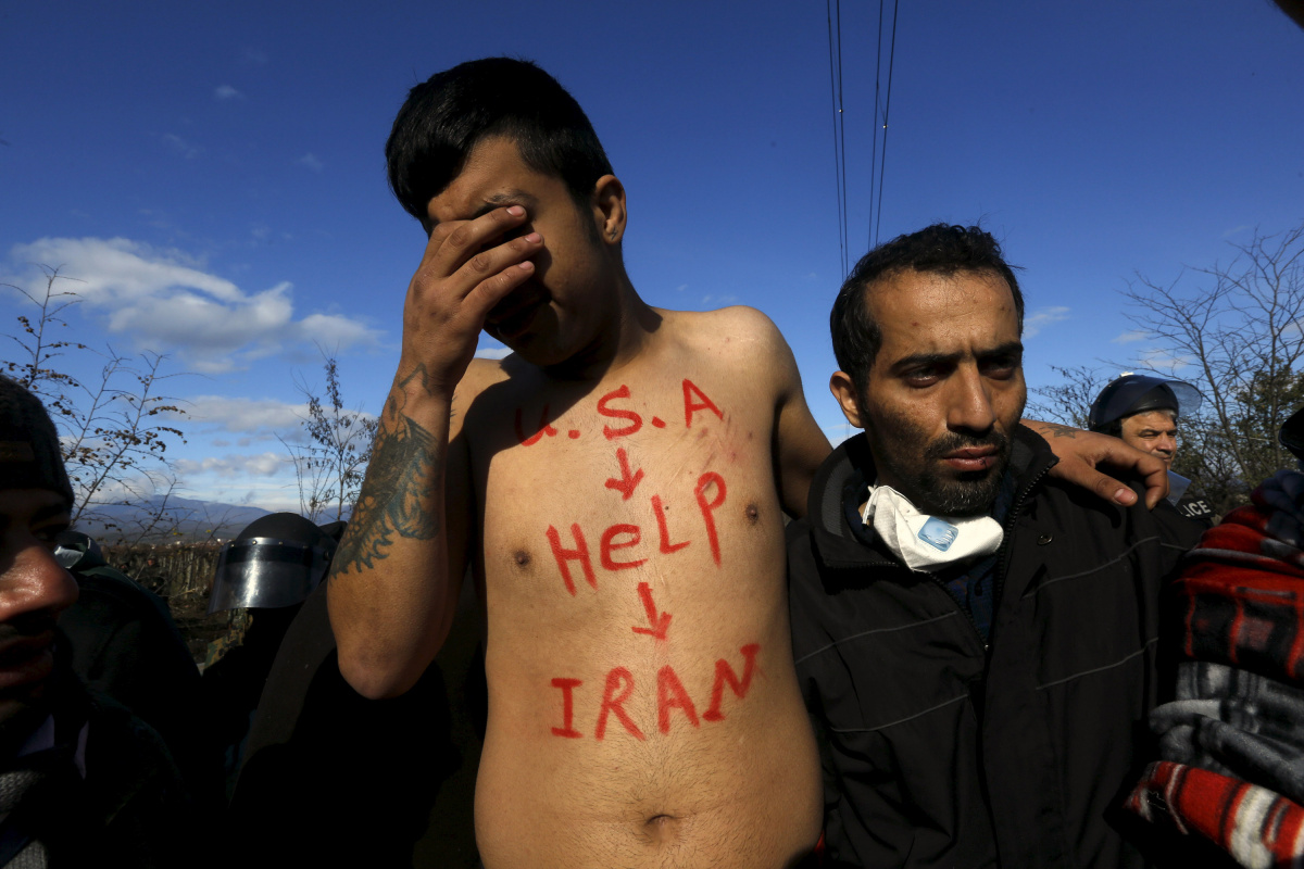"""A stranded Iranian migrant with a slogan reading """"USA help Iran"""" written on his body, cries during a protest at the Greek-Macedonian borders near the village of Idomeni, Greece"""