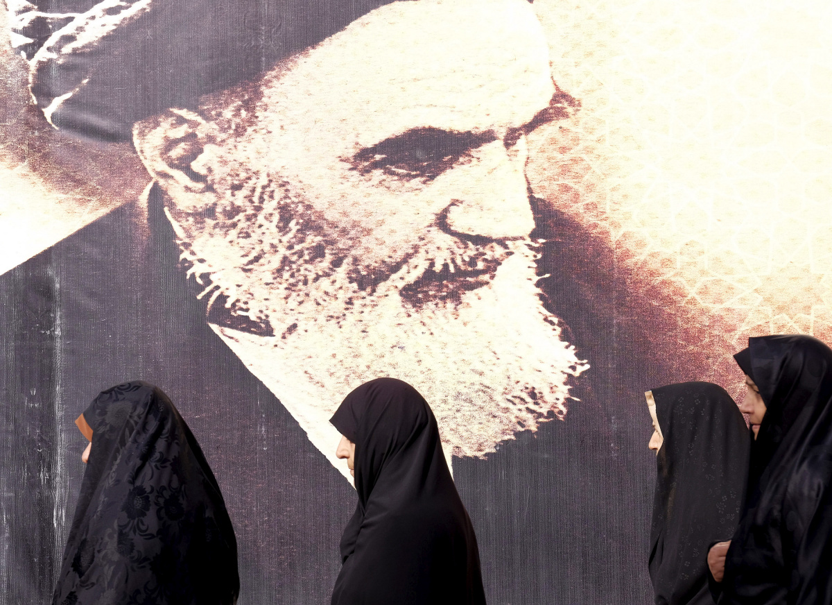 Iranian women walk past a poster of Iran's late leader Ayatollah Ruhollah Khomeini during the anniversary ceremony of Iran's Islamic Revolution in Behesht Zahra cemetery, south of Tehran