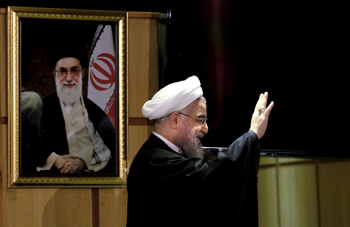 Iranian President Hassan Rouhani waves as he stands next to a portrait of Iran's Supreme Leader Ayatollah Ali Khamenei, after he registered for February's election of the Assembly of Experts, the clerical body that chooses the supreme leader, at Interior Ministry in Tehran