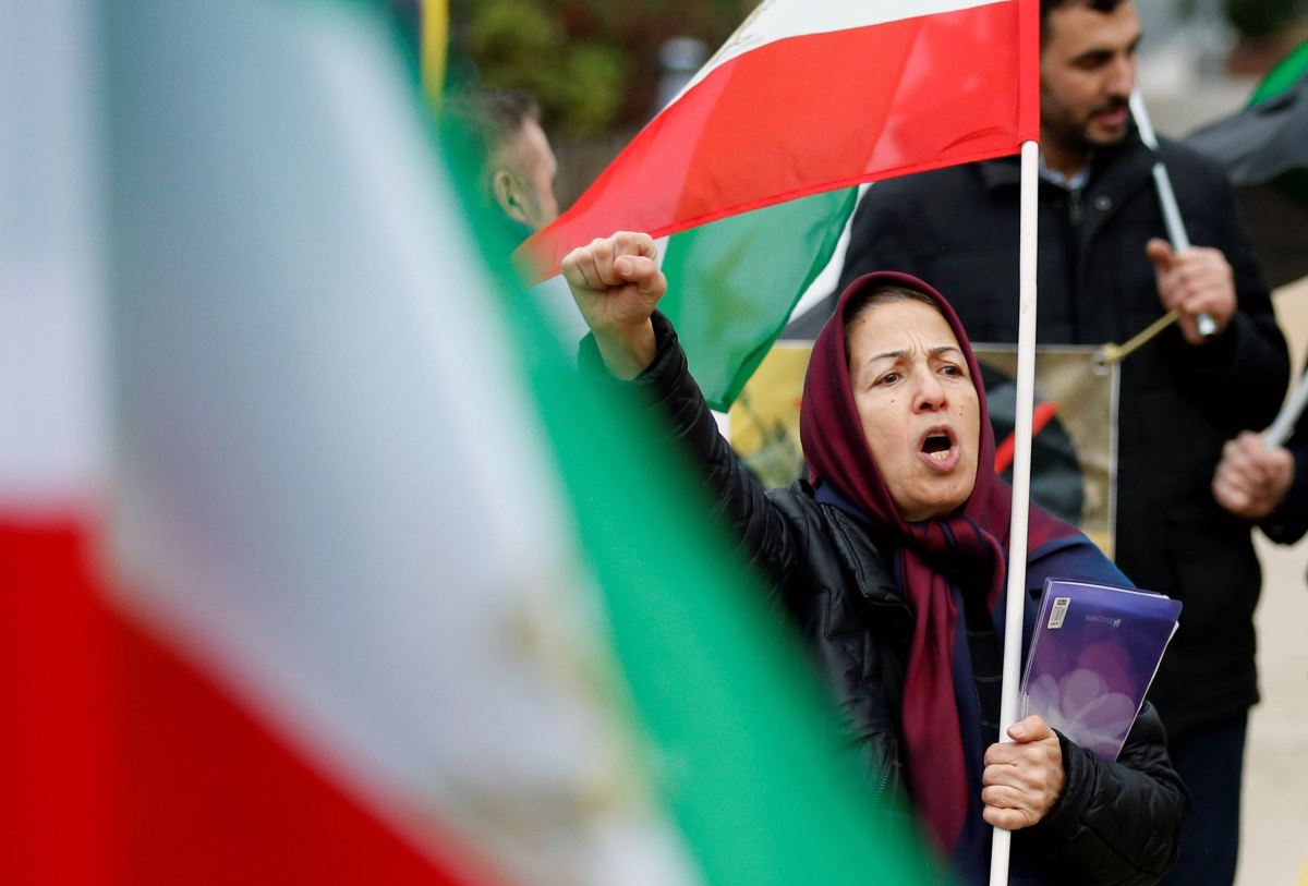 An opponent of Iranian President Rouhani chants slogans during a protest outside the EU Council in Brussels