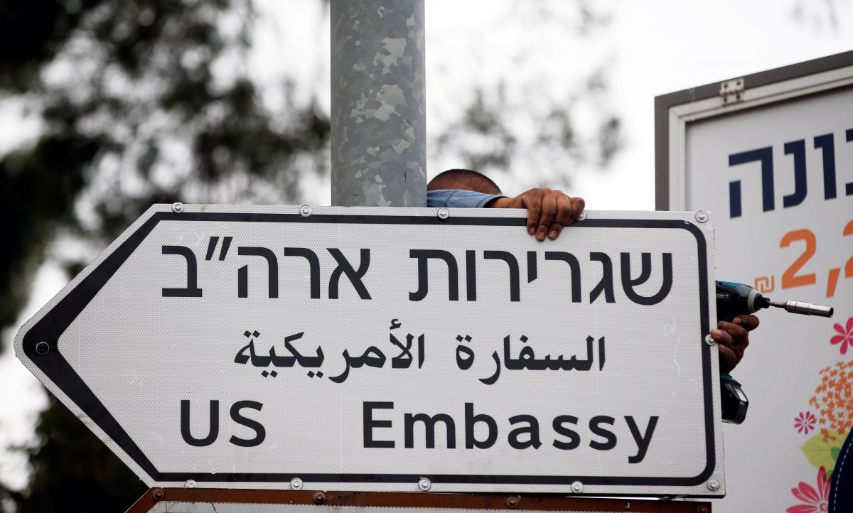 A worker hangs a road sign directing to the U.S. embassy, in the area of the U.S. consulate in Jerusalem