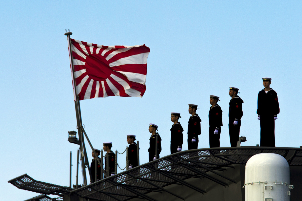 Sailors stand on the deck of the Izumo warship as it departs from the harbour of the Japan United Marine shipyard in Yokohama, south of Tokyo