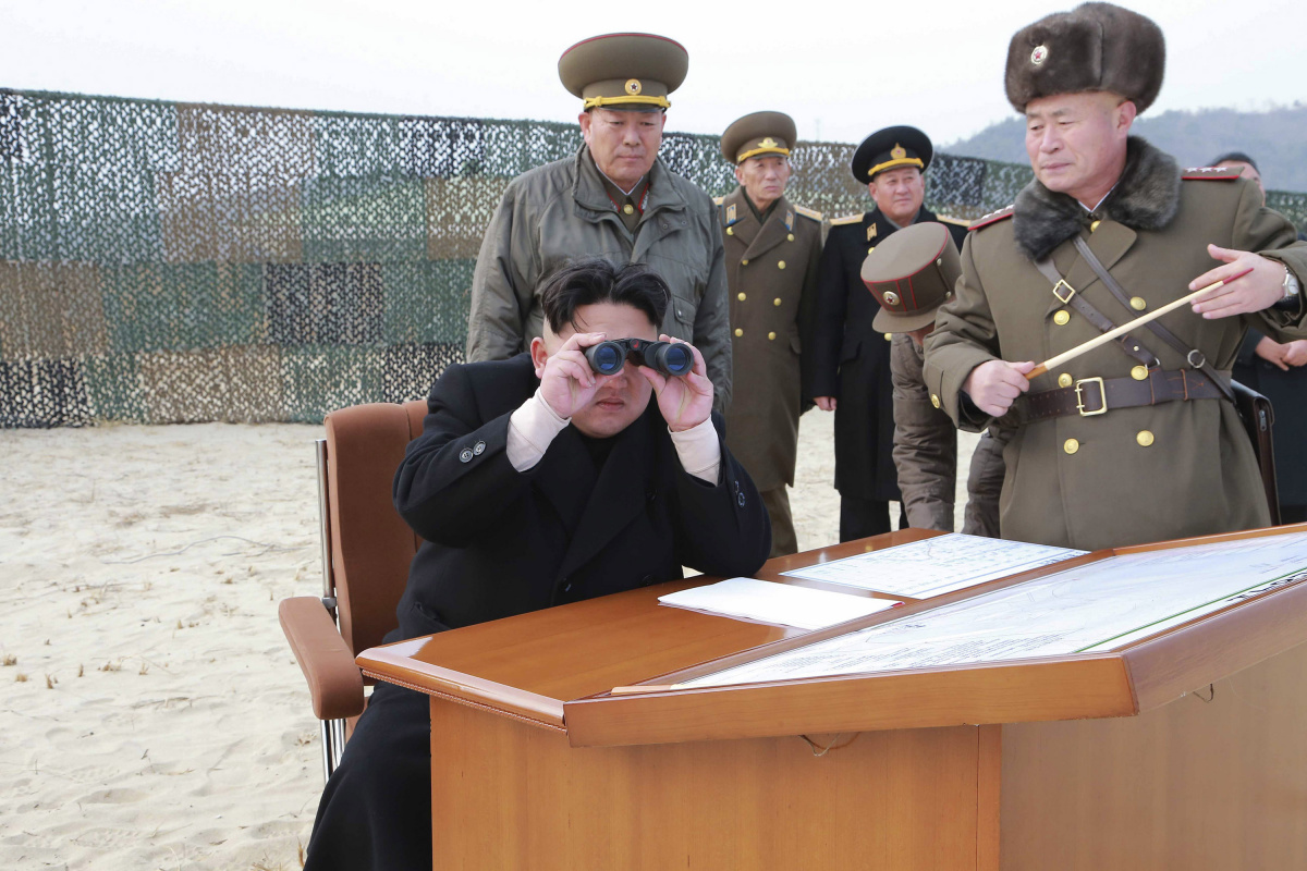 North Korean leader Kim Jong Un looks through a pair of binoculars as he guides the multiple-rocket launching drill of women's sub-units under KPA Unit 851