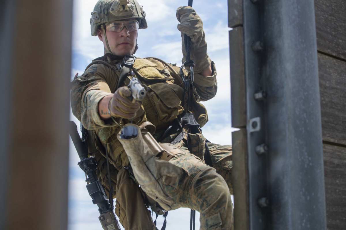 Marine simulates attacking a target through a window while rappelling down a rappel tower. Flickr/U.S. Department of Defense