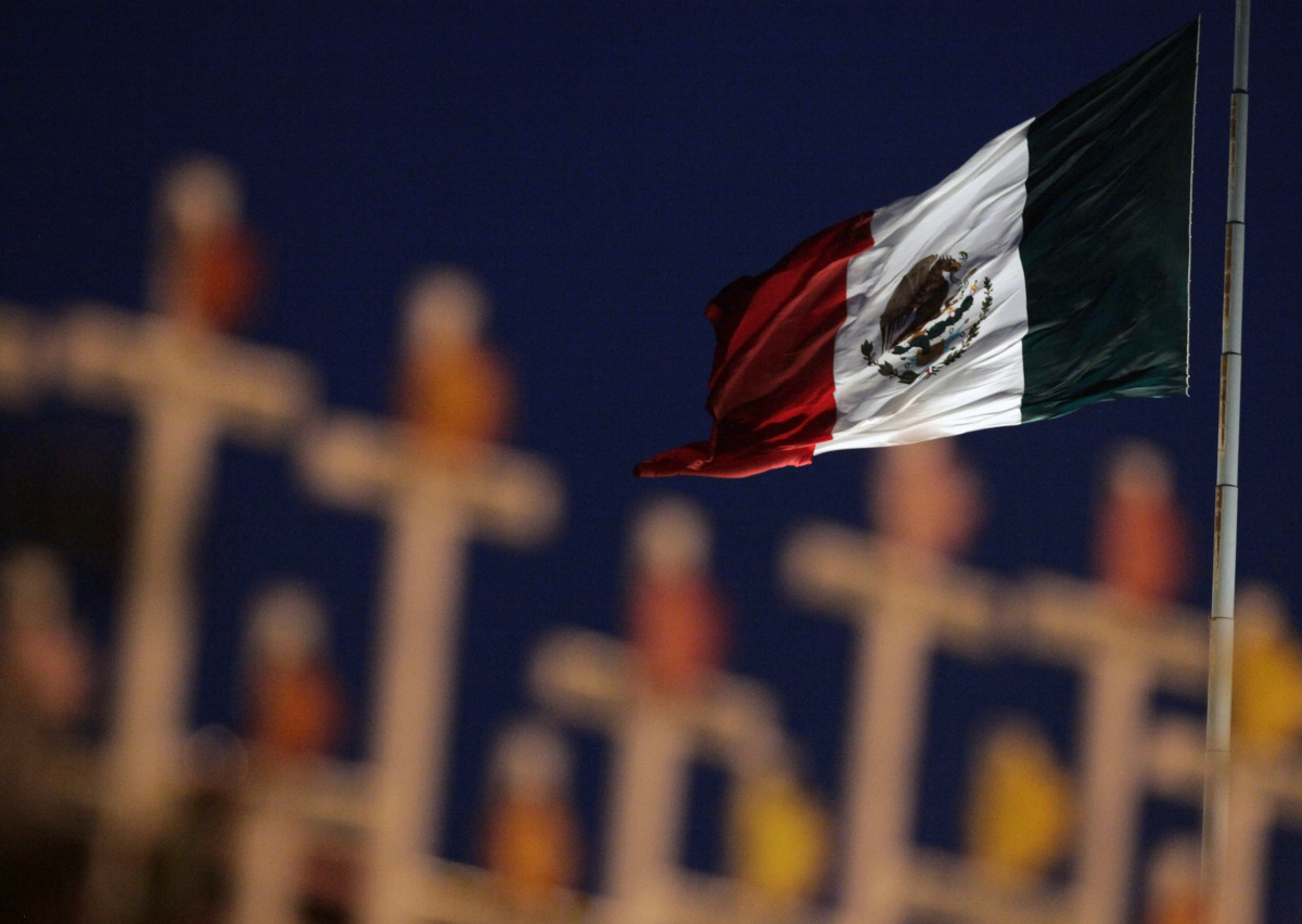 A Mexican national flag waves in front of crosses bearing the names of victims of an arson attack at a casino during an event marking the anniversary of those who died in Monterrey August 25, 2012