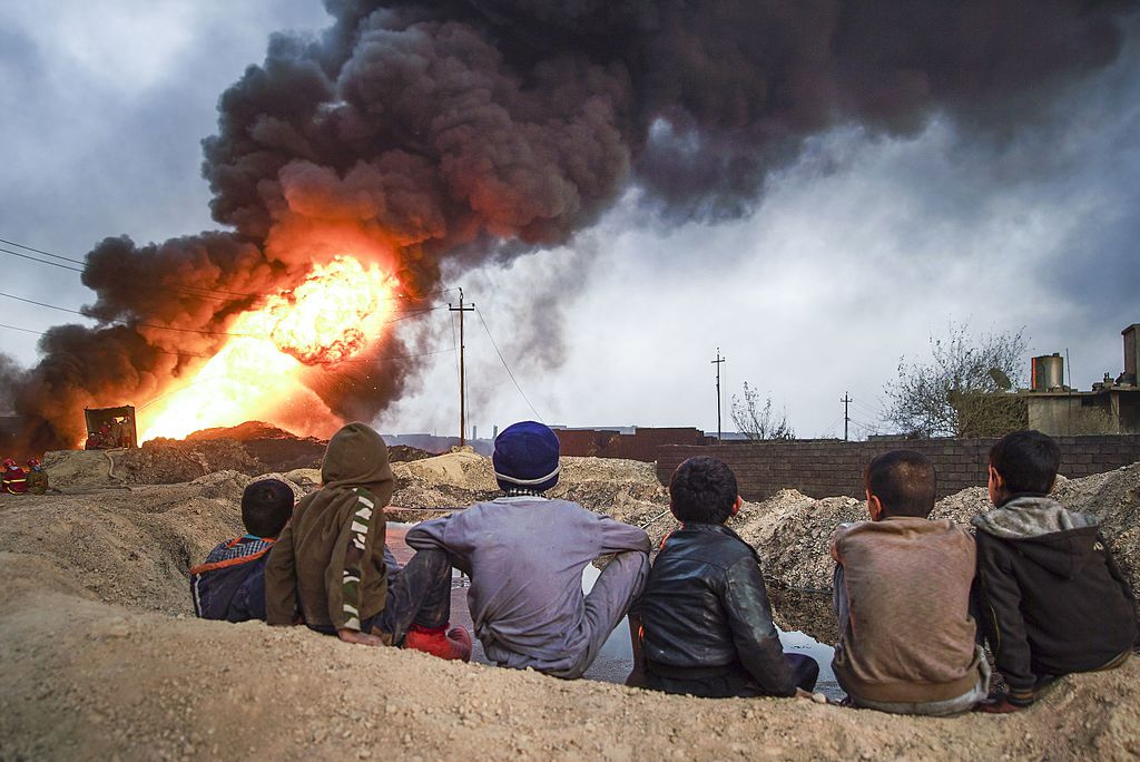 Local boys observing cityscape of Qayyarah on fire, Mosul District, Iraq. Wikimedia Commons/Creative Commons/Mstyslav Chernov