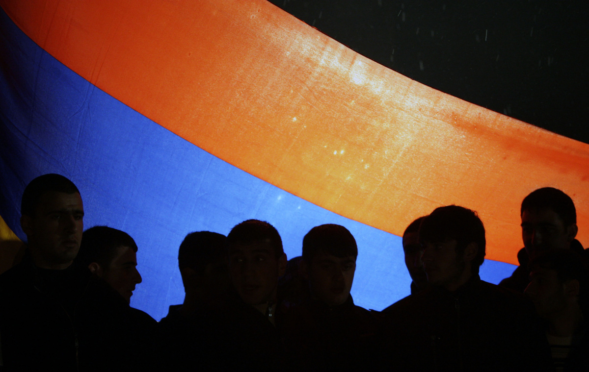 People are silhouetted against the Armenian national flag during a march marking the anniversary of the 1915 mass killings of Armenians in the Ottoman Empire, in Yerevan