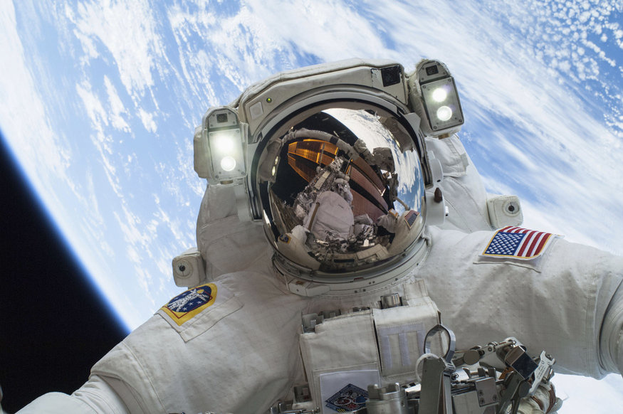 Astronaut Mike Hopkins, Expedition 38 Flight Engineer, is shown in this handout photo provided by NASA as he participates in the second of two spacewalks which took place on December 24, 2013, released on December 27, 2013. The scheduled spacewalks were designed to allow the crew to change out a faulty water pump on the exterior of the Earth-orbiting International Space Station. He was joined on both spacewalks by NASA astronaut Rick Mastracchio, whose image shows up in Hopkins' helmet visor. REUTERS/NASA/H