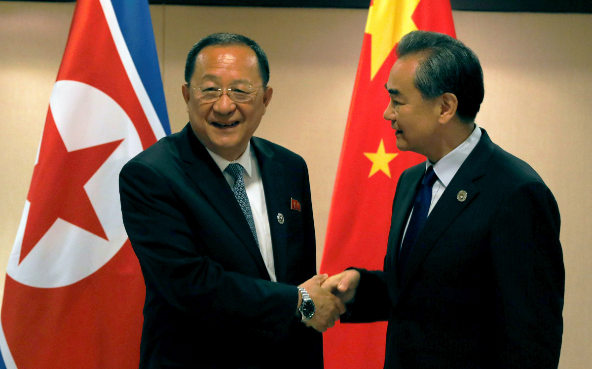 China's Foreign Minister Wang Yi (R) shakes hands with North Korea's Foreign Minister Ri Yong Ho before their bilateral meeting on the sidelines of the 50th Association of Southeast Asia Nations (ASEAN) Regional Forum (ARF) in Manila, Philippines