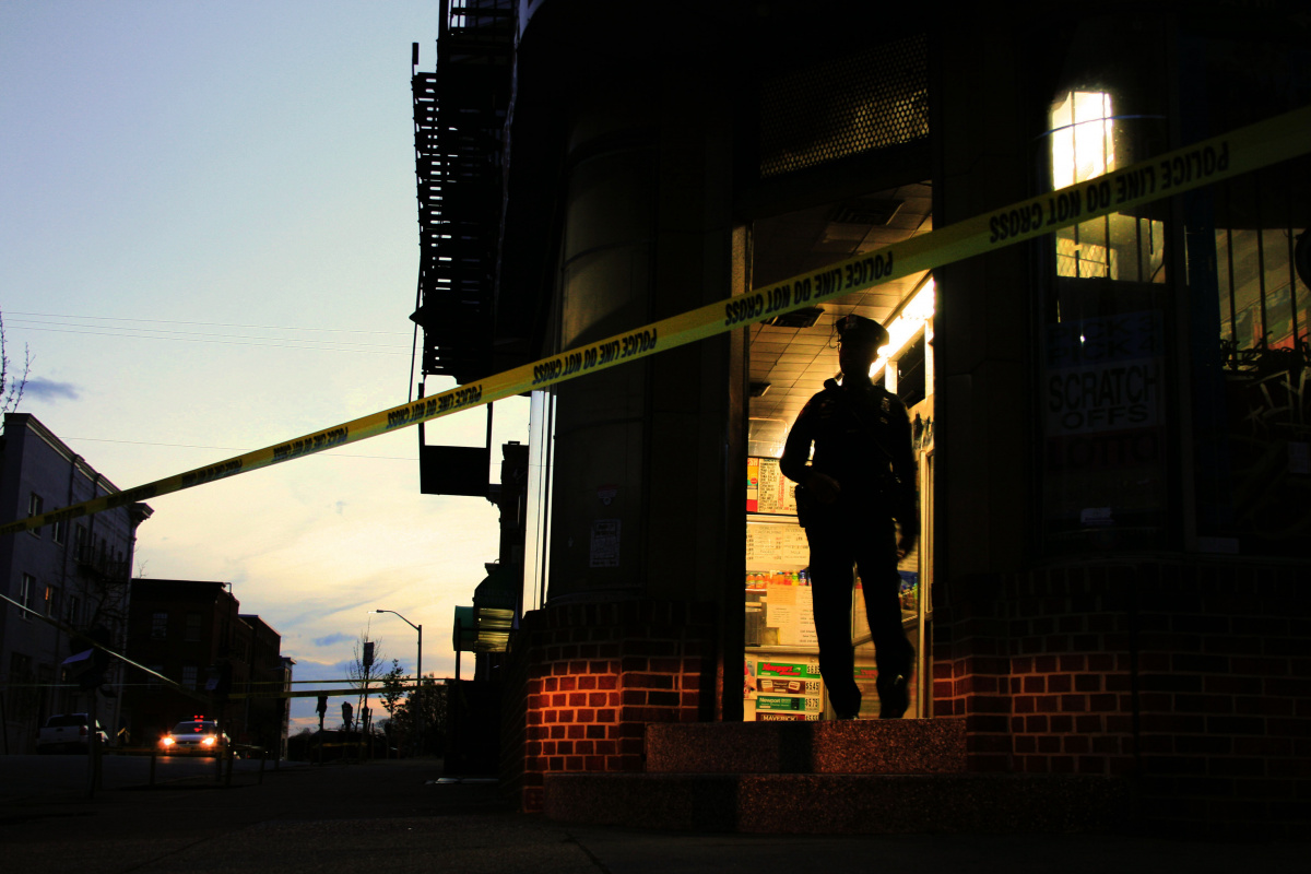 Baltimore police officer stands guard at the site of a shooting. Maggie Ybarra