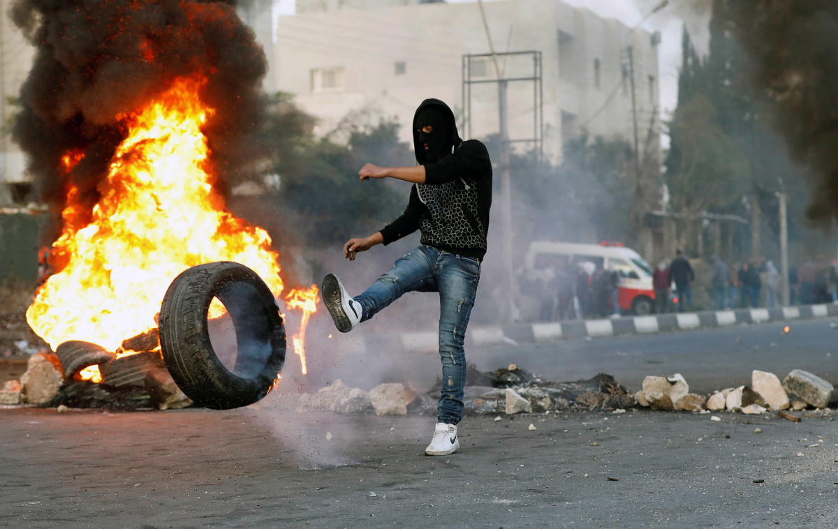 Palestinian demonstrator kicks a burning tire during clashes with Israeli troops at a protest near the West Bank city of Nablus