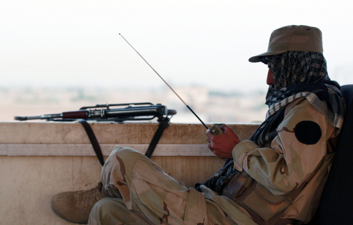 A private security organization contractor listens to a radio during his duty at guard tower in Camp Nathan Smith in Kandahar City