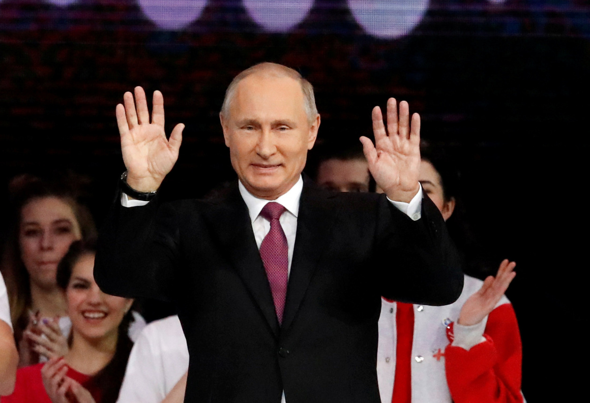 Russian President Putin greets the audience at the congress of volunteers in Moscow